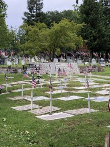 Many flags atop crosses marking graves of veterans donated to the cemetery.